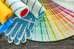 Paint rollers safety gloves color palette on wooden board.  stock photo