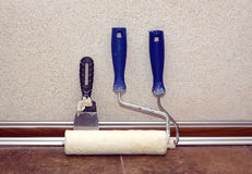 Paint rollesr and trowel stands in a room at baseboard near wall Stock Photography