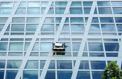 Paint on the sky. Workers on scaffold performing window cleaning on a tall glass building royalty free stock photo