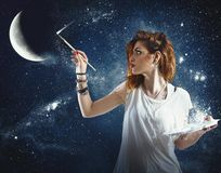 Paint the sky. Girl paints the moon and the stars Stock Photos