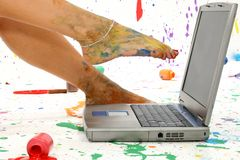Paint Splash. Woman's foot on laptop. Surounded by splattered paint royalty free stock photography