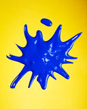 Paint Splash. Blue paint splashed over yellow background Royalty Free Stock Images