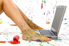 Paint Splash. Woman's foot on laptop. Surounded by splattered paint stock photo