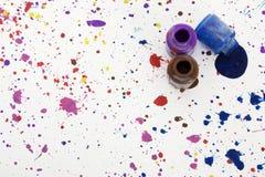 Paint Splatter on Floor. Jars of paint on floor; purple, blue, brown Stock Photo