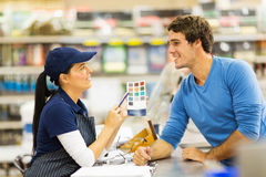 Paint store assistant helping customer. Pretty paint store assistant helping customer choose paint color Stock Image