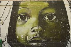 Venezuelan urban art, Maracay. Paint on a street wall in Maracay city, Venezuela. South america. Face of children looking you Royalty Free Stock Images