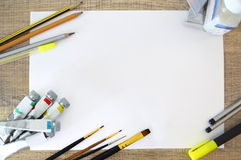 Paint supplies, pencils, brush on white paper Royalty Free Stock Images