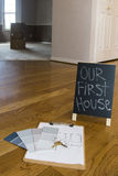 Paint swatches and house plans on floor with first house sign. Paint swatches and home plans with keys to new house with first house sign stock images