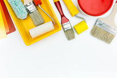 Paint tools and accessories for home renovation. Paint roller, tray, brushes, and paint can with color swatch stock images