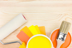Paint tools with color guide on wooden background. Brush and roller with color guide and paint can stock image