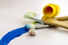 Paint tube and brushes. Yellow paint tube and brushes, seashell, brush stroke. Art supplies stock image