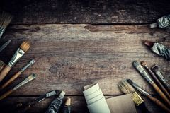 Paint tubes, brushes for painting and palette knifes on old wooden background. Stock Image