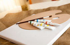 Paint tubes, pallet and brush lying on table at living room Stock Photo