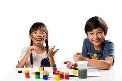 Paint. Two smiling little kids at the table draw with water color, Isolated over white royalty free stock image