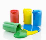 Paint of various colors spilled. Open containers of paint in primary colors spilled and mixed stock images
