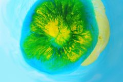 Paint in water. Blue, green and yellow paint in water Royalty Free Stock Images