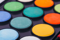 Paint watercolors pallet. Close up on black royalty free stock photo