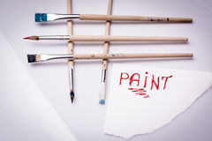 Paint word on a white sheet and paint brushes Royalty Free Stock Photo