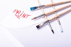 Paint word on a white sheet and paint brushes Royalty Free Stock Photography