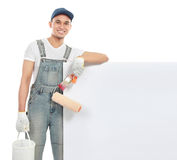Paint worker with blank banner. Portrait of paint worker with tool hold a big blank white banner Stock Photo