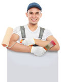 Paint worker with tool hold a blank banner. Handsome paint worker with tool hold a blank banner Royalty Free Stock Photos