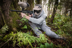 Paintball in the forest. Active paintball sport player in the forest with protective clothing Stock Images