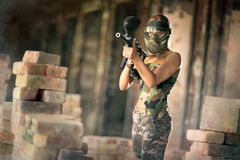 Paintball game in runs. Woman in camouflage  uniform with mask, paintball game in runs Stock Image