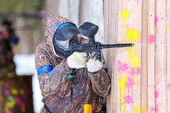Paintball game in winter. Cool shooter behind fortification. Paintball game in winter. Cool shooter behind fortification outdoors royalty free stock image