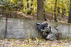 Paintball girl behind wall Stock Image