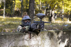 Paintball girl shooting enemies from cover Stock Images
