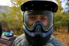 Girl in camouflage and paintball mask stock photography