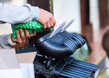 Paintball guns on the table. a man is filling gun with a balls. paintball games can be played on indoor or outdoor fields royalty free stock images