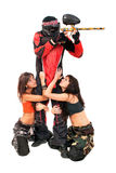 Paintball hero. Paintball player with girls on a knees around him Royalty Free Stock Image