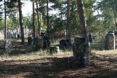 Paintball hideout. Forest territory with barrels and tires with multi-colored blots for a team game of war, fenced with a wooden. Paintball hideout background stock photos