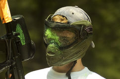 Paintball Mask. Green paint spattered on the mask of a paint ball player Stock Image