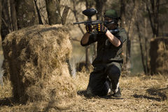 Paintball player. A paintball player shoots from behind cover simulating military combat royalty free stock image
