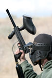 Paintball player. Paintball - teen paintballer with gun, wearing protective mask. focus on head Royalty Free Stock Images