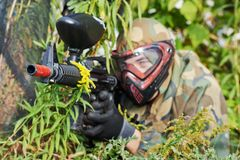 Paintball player. Adrenalin paintball player in protective uniform and mask aiming gun before shooting in summer Stock Photography