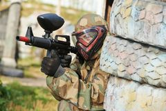 Paintball player. Adrenalin paintball player in protective uniform and mask aiming gun before shooting in summer Royalty Free Stock Image