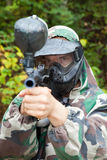 Paintball player aiming looks in face in forest Stock Images