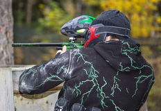 Paintball player aiming. Paintball player in uniform with splashes aiming outdoors Royalty Free Stock Photo
