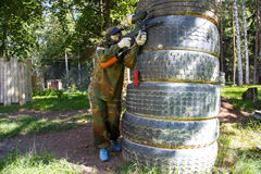 Paintball player behind giant truck tire fortification Royalty Free Stock Photos