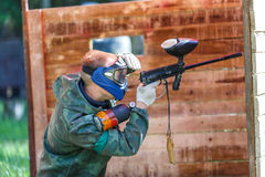 Paintball player in blue helmet shooting from paint gun Royalty Free Stock Photography