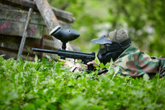Paintball player in camouflage lies in ambush Stock Images