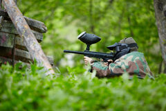 Paintball player in camouflage sits in ambush Royalty Free Stock Images