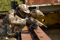 Paintball player in camouflage uniform. Outdoors stock image