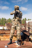 Paintball player in camouflage uniform. In abandoned place stock images