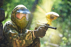 Paintball player direct hit. Paintball sport player wearing protective mask aiming gun and shotted down with paint splash in summer Stock Photography