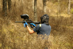 Paintball player in forest. Paintball player with marker and mask in forest stock image