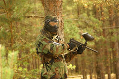 Paintball player in forest. Paintball player with marker and mask in forest royalty free stock images